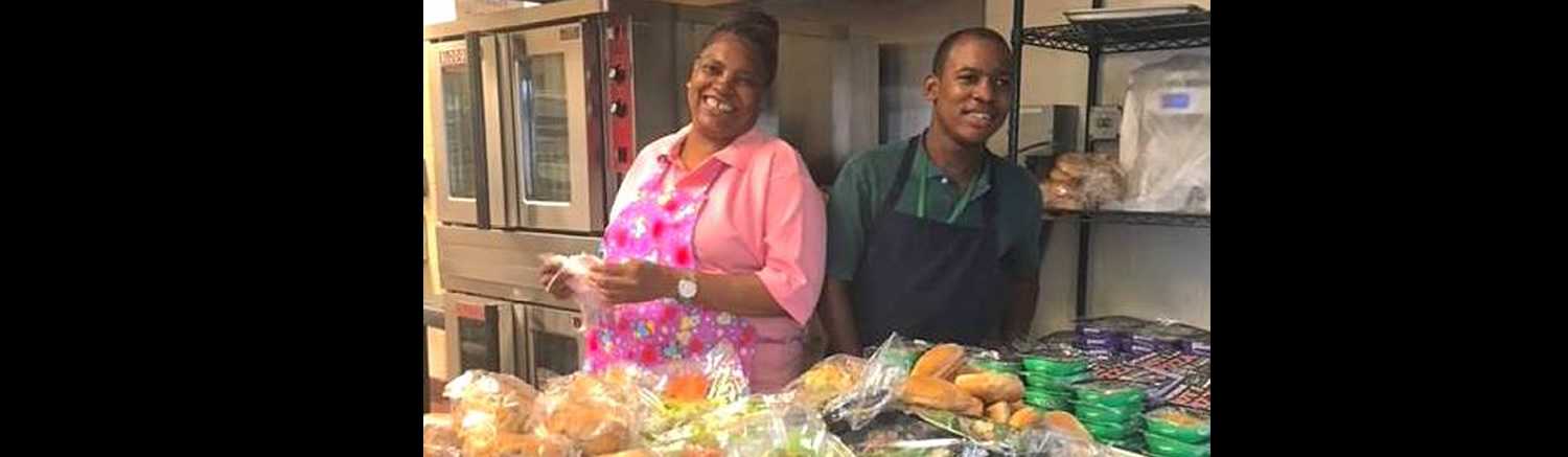 Stephen assists a woman in preparing lunch for school children